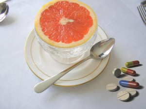 Bowl of grapefruit and pills on table