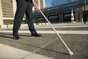 blind person walking down street with cane