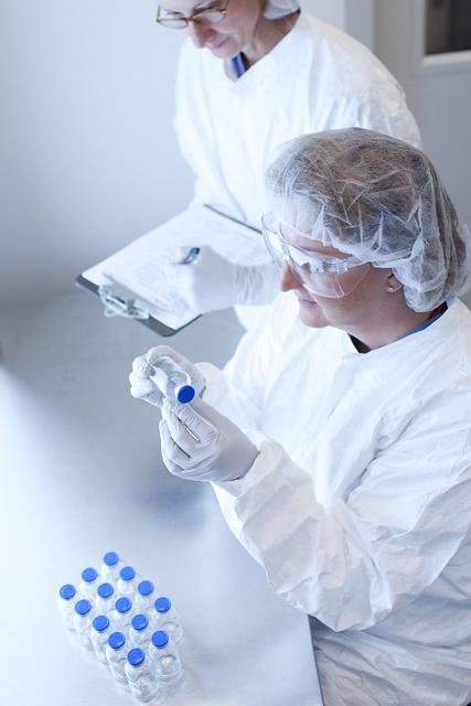 scientists examining glass vials